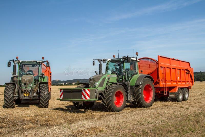 Due trattori moderni di Fendt che tirano i rimorchi arancio fotografia stock libera da diritti