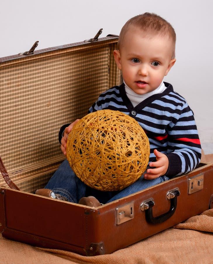 Due, tre anni del neonato portano la grande valigia isolata su w immagini stock