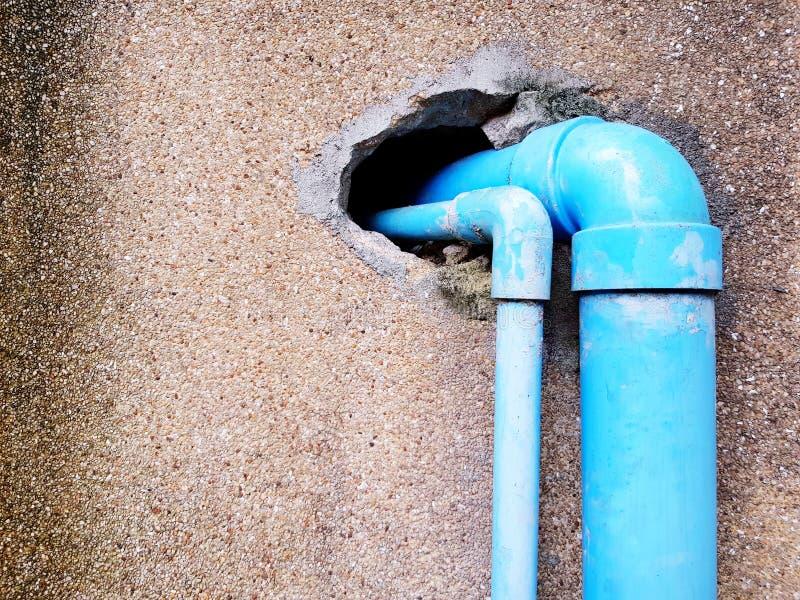 Due tubature dell'acqua di plastica blu inserite nel foro del muro di cemento marrone incrinato fotografia stock