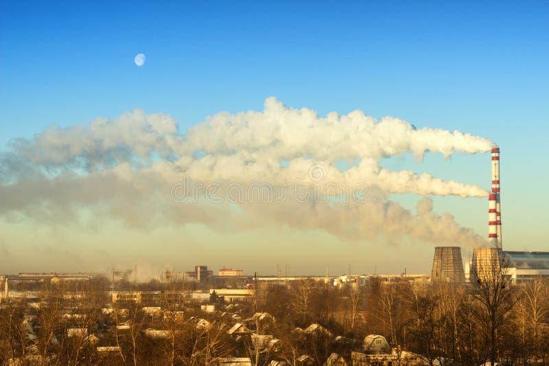 Due tubi fumano nella centrale elettrica termica contro il cielo gelido blu nell'inverno, la luna immagine stock