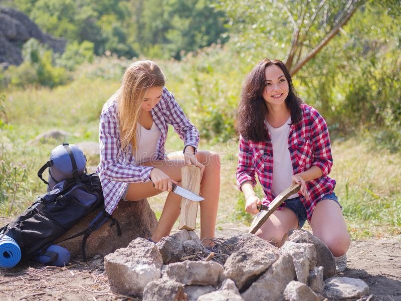 Due turisti provano a fare un fuoco per cucinare il loro proprio alimento Le vacanze estive negli amici della foresta sono andato fotografie stock libere da diritti