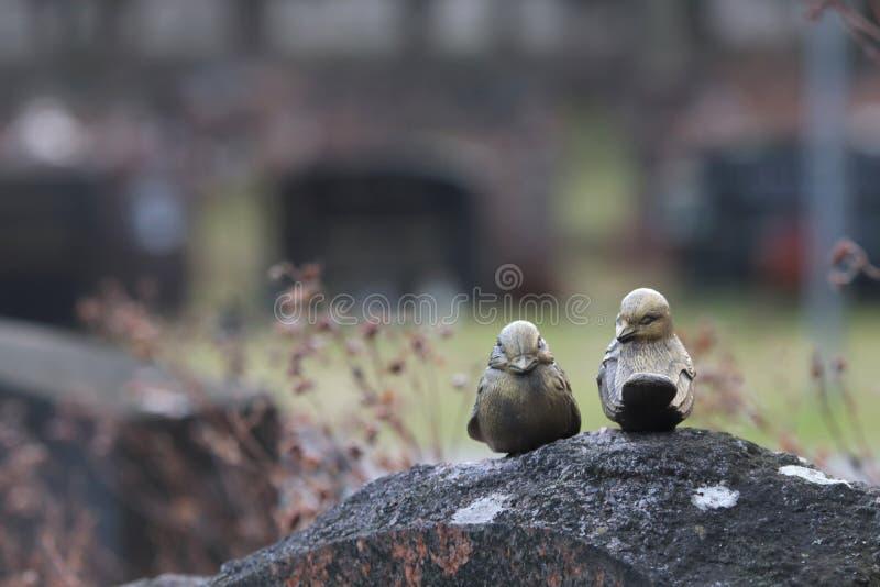 Due uccelli metallici decorativi su una carrucola immagine stock