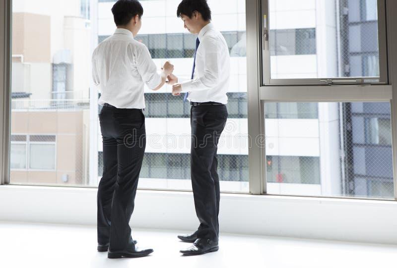 Due uomini al supporto che parlano insieme nell'ufficio fotografie stock libere da diritti
