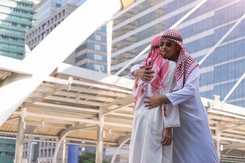 Due uomini arabi che si abbracciano, avendo raduno caldo fotografie stock