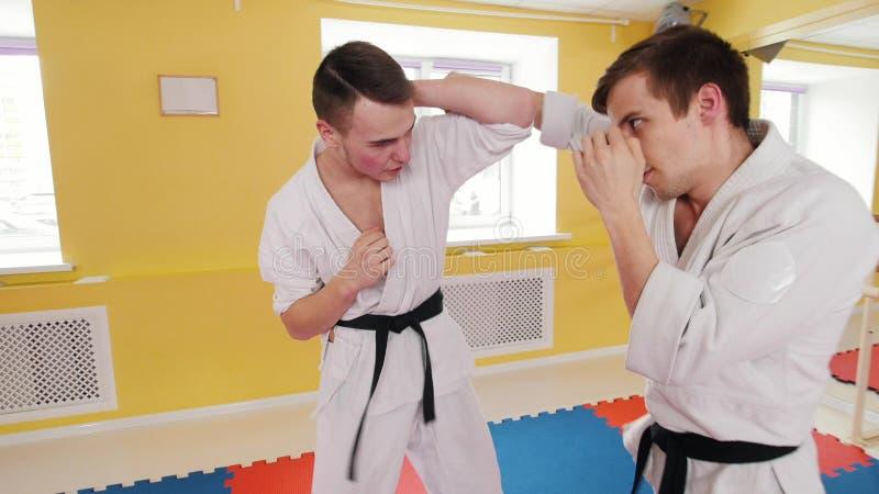 Due uomini atletici che preparano le loro abilit? di aikidi nello studio Proteggendo dal colpo immagine stock libera da diritti