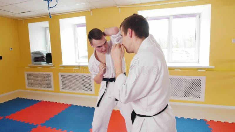 Due uomini atletici che preparano le loro abilit? di aikidi nello studio protezione fotografia stock