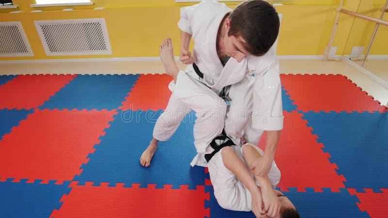 Due uomini atletici che preparano le loro abilit? di aikidi nello studio Un uomo che si trova sul pavimento e che protegge dal co fotografie stock libere da diritti