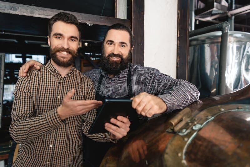 Due uomini barbuti adulti contano sullo scorrimento dell'acqua della compressa per fare brewery Elaborazione della birra immagini stock