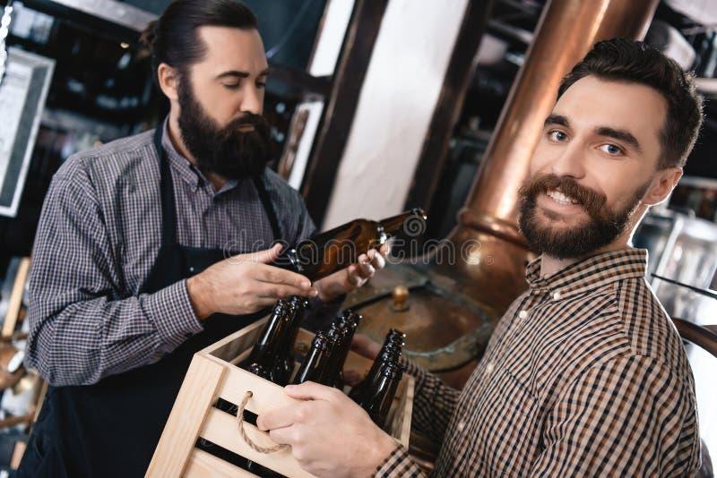 Due uomini barbuti adulti controllano la qualità del vetro della bottiglia di birra alla fabbrica di birra Processo di fabbricazi fotografia stock