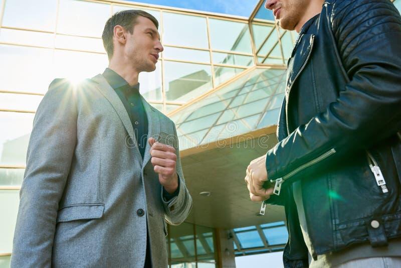 Due uomini bei che chiacchierano all'aperto fotografia stock libera da diritti
