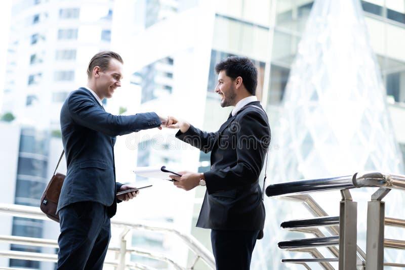 Due uomini bei di affari parlano e dando l'urto del pugno sulla città immagini stock