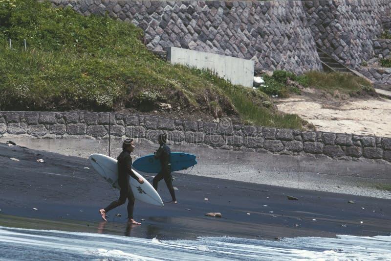 Due uomini che camminano su una spiaggia nera per praticare il surfing fotografie stock libere da diritti