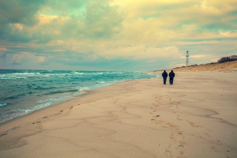 Due uomini che camminano sulla spiaggia nell'inverno fotografie stock libere da diritti