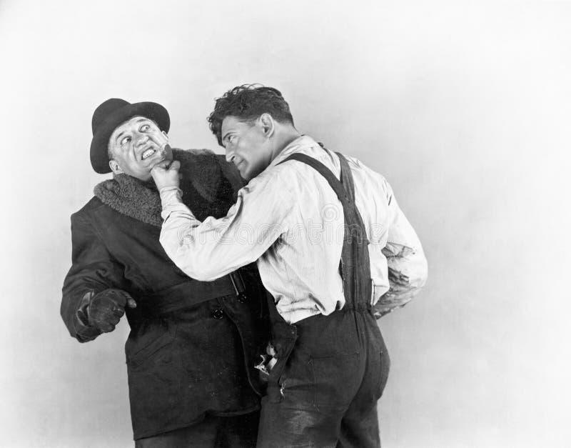 Due uomini che combattono a vicenda (tutte le persone rappresentate non sono vivente più lungo e nessuna proprietà esiste Garanzi fotografia stock
