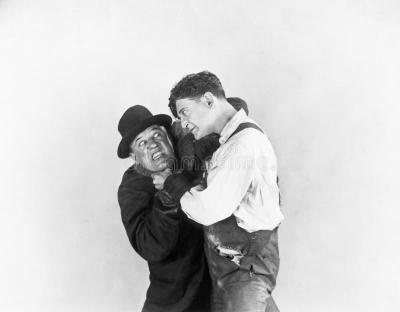 Due uomini che combattono a vicenda (tutte le persone rappresentate non sono vivente più lungo e nessuna proprietà esiste Garanzi fotografia stock libera da diritti