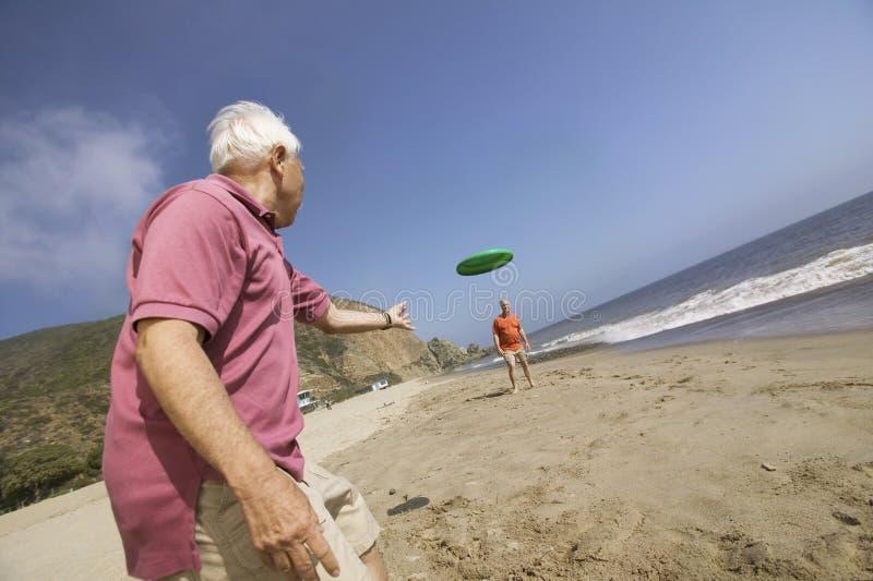 Due uomini che giocano con il disco di volo sulla spiaggia immagine stock