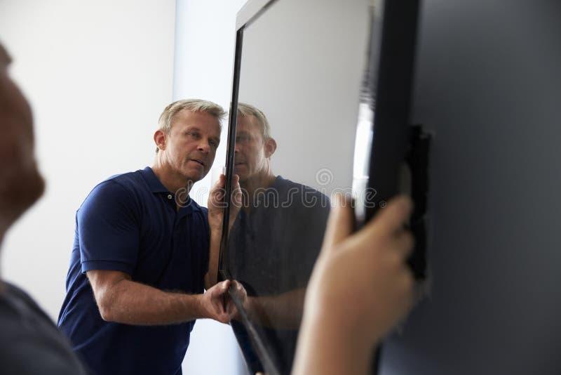 Due uomini che misura la televisione dello schermo piano per murare fotografie stock libere da diritti