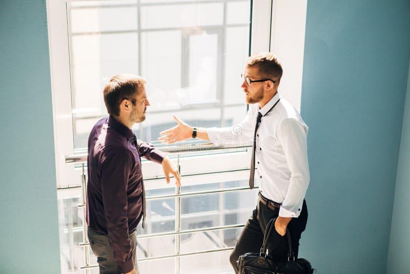 Due uomini che parlano nell'ingresso dell'ufficio immagine stock