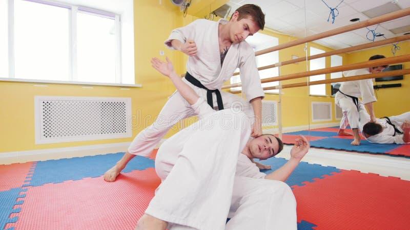 Due uomini che preparano le loro abilit? di aikidi nello studio Un uomo che si trova sul pavimento e che protegge dal colpo fotografia stock