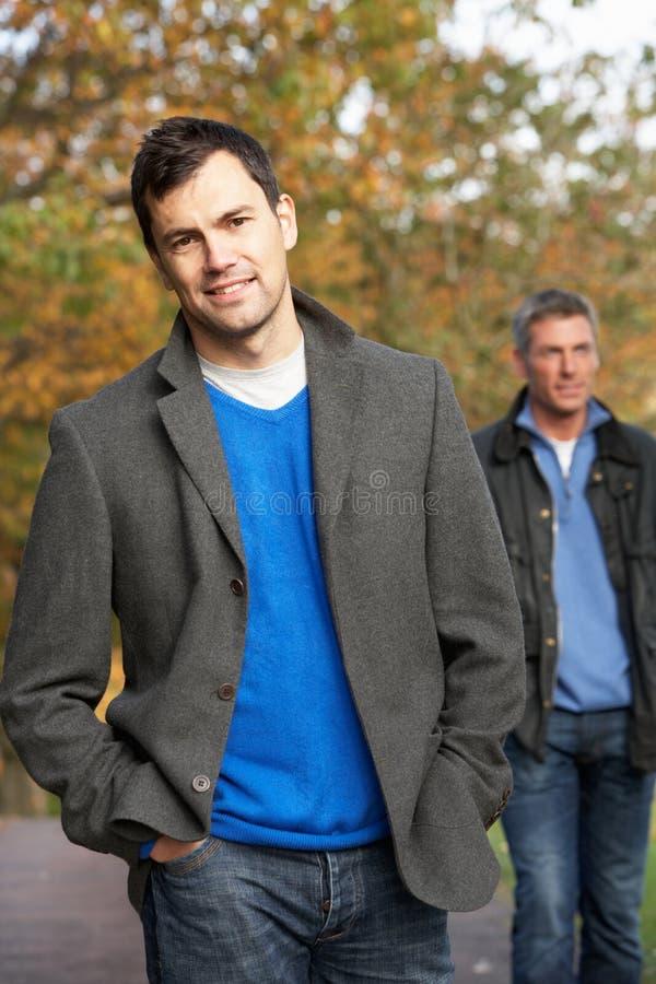 Due uomini che si levano in piedi all'esterno nel terreno boscoso di autunno immagine stock libera da diritti