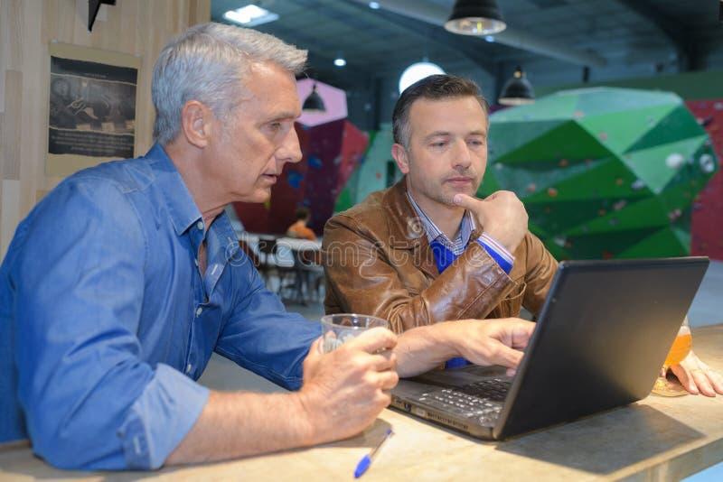Due uomini che utilizzano computer portatile nella barra del caffè immagini stock libere da diritti