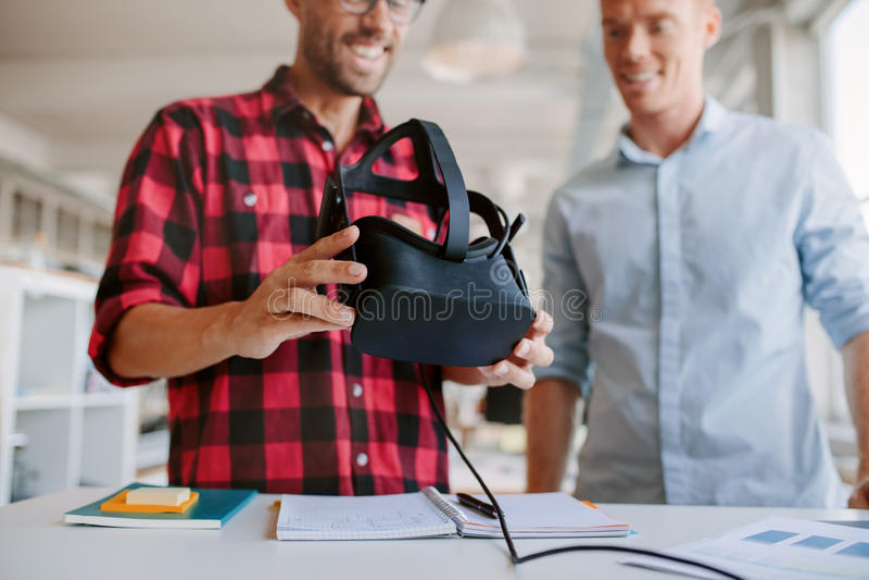Due uomini che utilizzano gli occhiali di protezione di realtà virtuale nell'ufficio fotografia stock