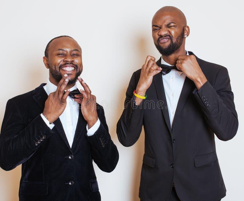 Due uomini d'affari afroamericani in vestiti neri posa emozionale, gesturing, sorridenti farfallini d'uso fotografie stock libere da diritti