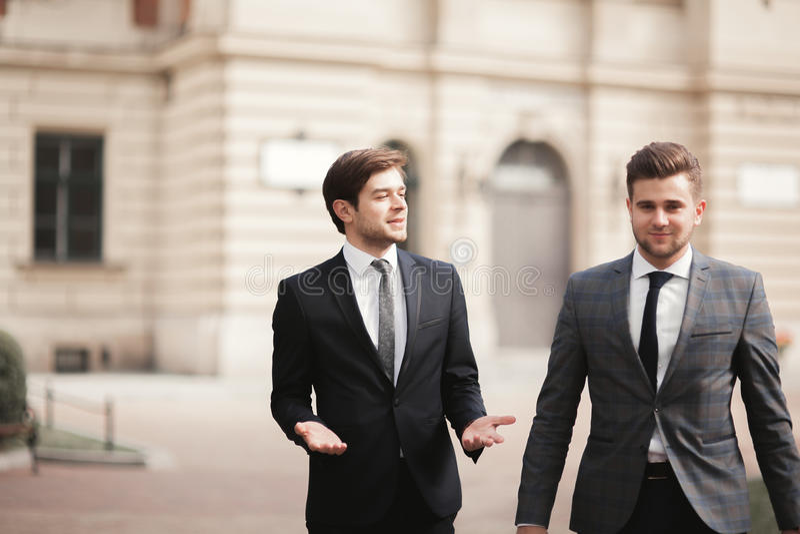 Due uomini d'affari alla moda che parlano e che sorridono all'aperto fotografia stock