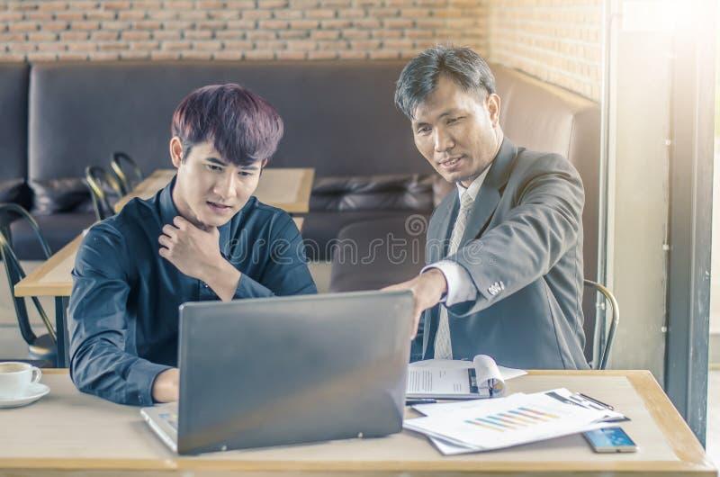 Due uomini d'affari attraenti che hanno una riunione con il computer portatile mentre mangiando caffè immagine stock
