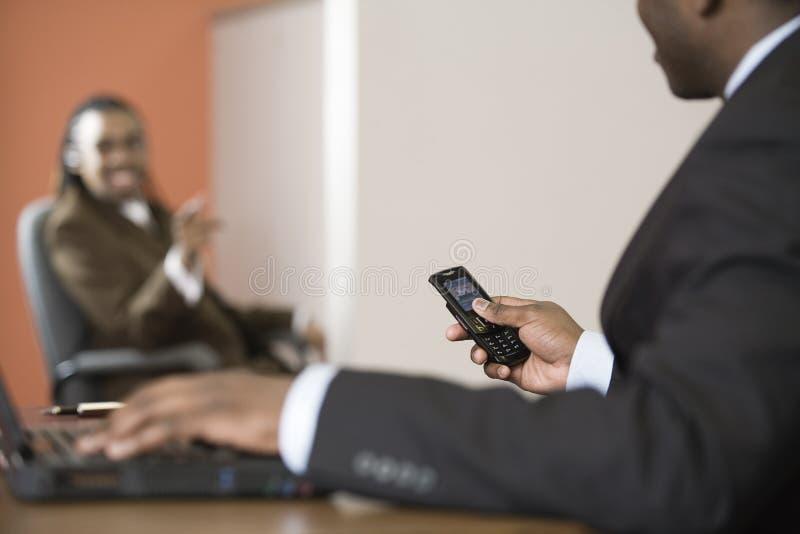 Due uomini d'affari che comunicano in un ufficio durante la cella fotografie stock libere da diritti