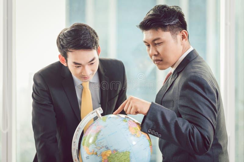 Due uomini d'affari che esaminano globo fotografia stock