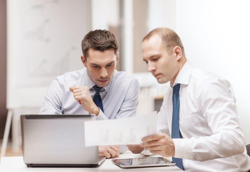 Due uomini d'affari che hanno discussione in ufficio immagine stock