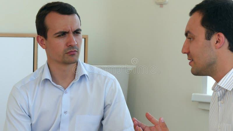 Due uomini d'affari che hanno discussione in ufficio e gesticolano immagine stock