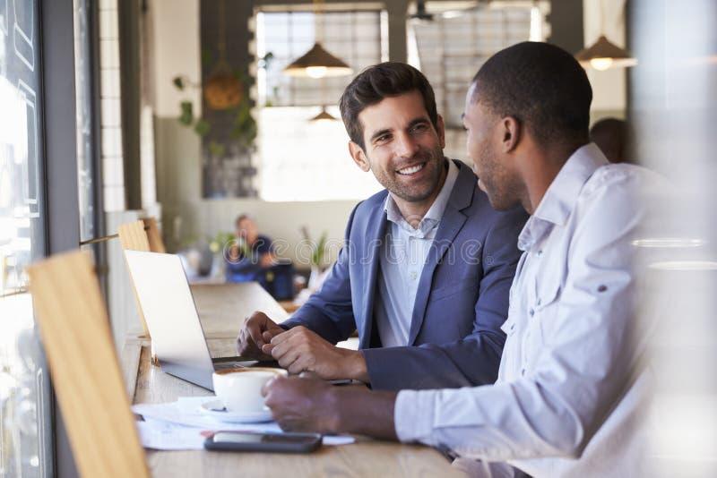 Due uomini d'affari che hanno riunione informale in caffetteria fotografia stock libera da diritti