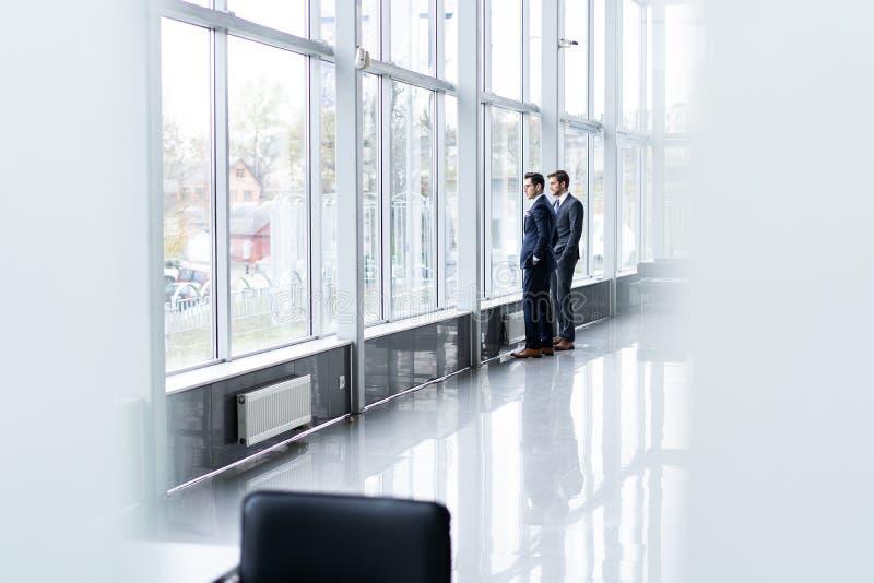 Due uomini d'affari che hanno riunione informale in corridoio dell'ufficio immagine stock