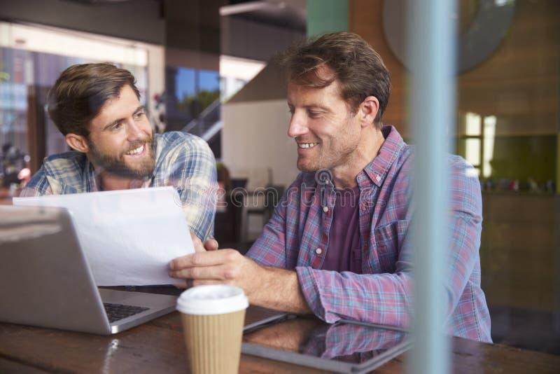 Due uomini d'affari che lavorano al computer portatile in caffetteria immagini stock libere da diritti