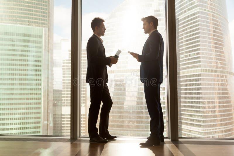 Due uomini d'affari che parlano finestra grande vicina diritta di negoziazione, ci immagine stock