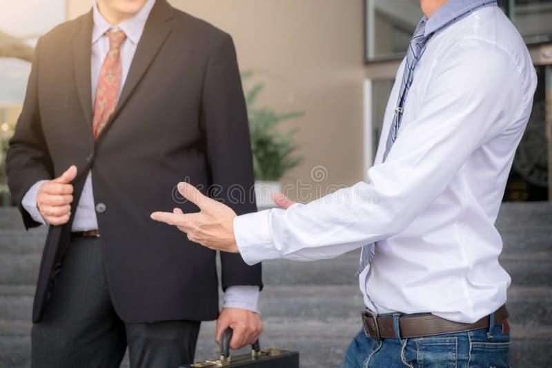 Due uomini d'affari che stanno parlanti fuori dell'ufficio, partne di affari fotografie stock libere da diritti