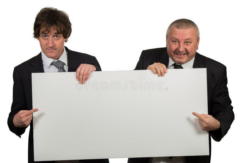 Due uomini d'affari che tengono un grande segno in bianco fotografie stock