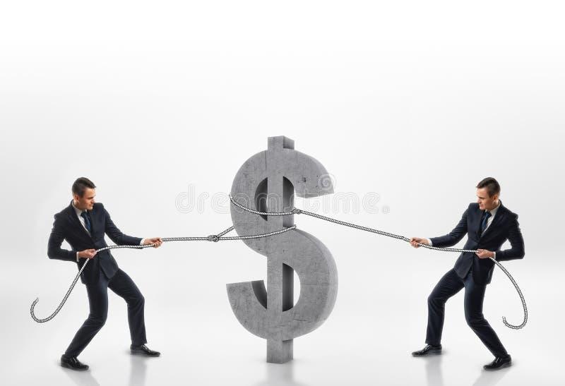 Due uomini d'affari che tirano il grande simbolo di dollaro del calcestruzzo 3d con le corde nelle direzioni opposte isolate su f fotografie stock