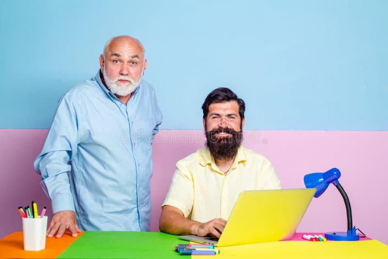 Due uomini d'affari che usano il computer discutono insieme notizie o film Due colleghi che lavorano insieme in ufficio a colori fotografia stock