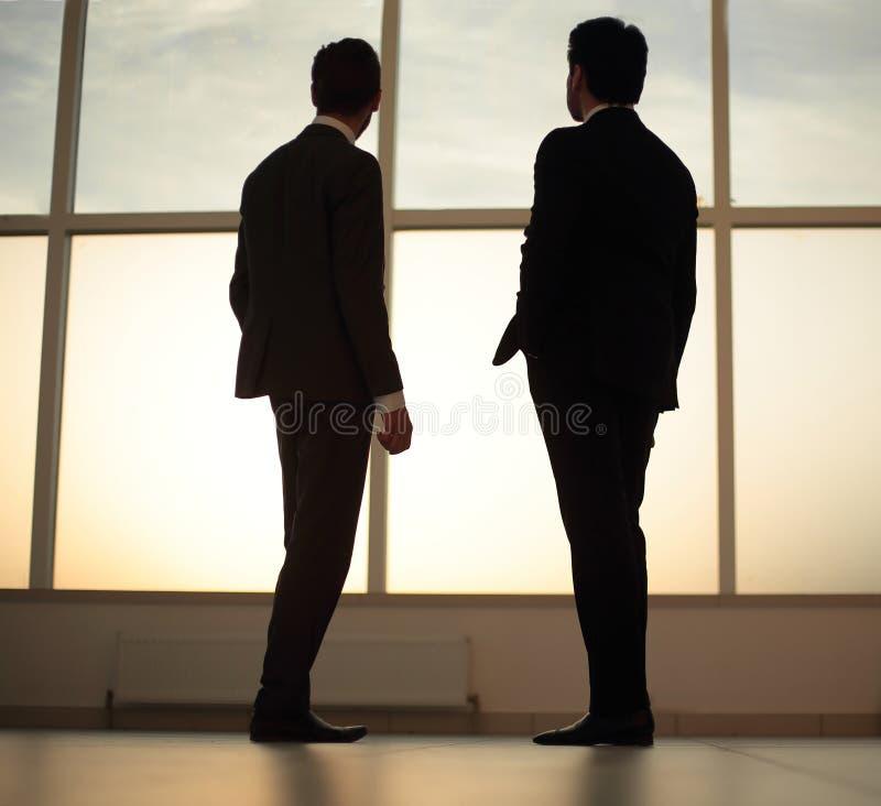 Due uomini d'affari esaminano la città dalla finestra del centro di affari fotografia stock libera da diritti