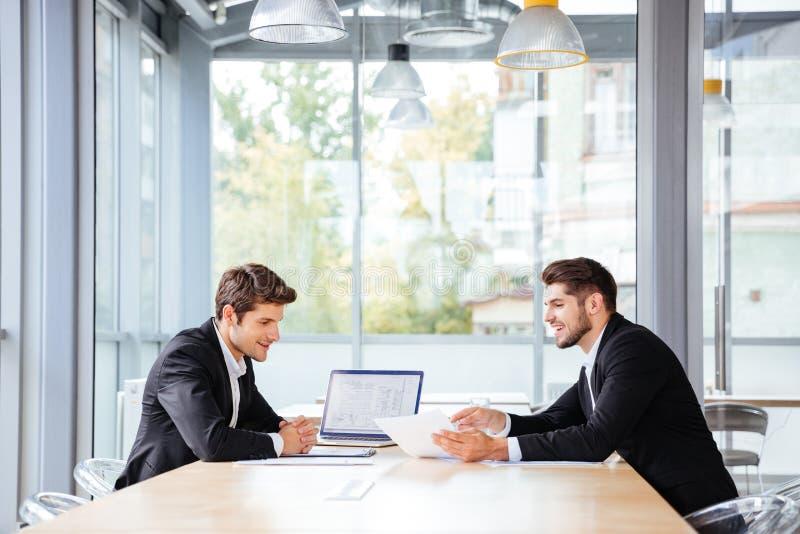 Due uomini d'affari felici che lavorano insieme facendo uso del computer portatile sulla riunione d'affari immagini stock libere da diritti