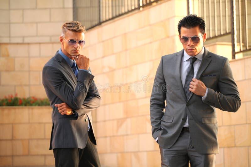 Due uomini d'affari in Front Near Wall, occhiali da sole immagine stock
