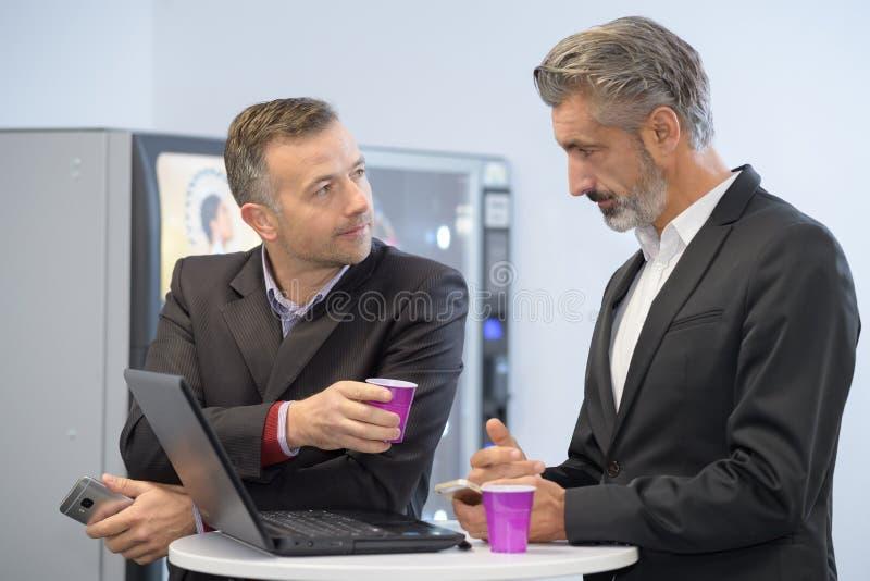 Due uomini d'affari giovani che mangiano caffè facendo uso del computer portatile immagine stock libera da diritti