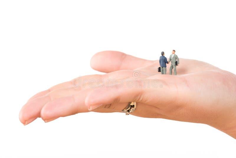 Due uomini d'affari miniatura che stringono le mani sulla mano femminile isolata su fondo bianco Affare di affari o concep di suc immagini stock