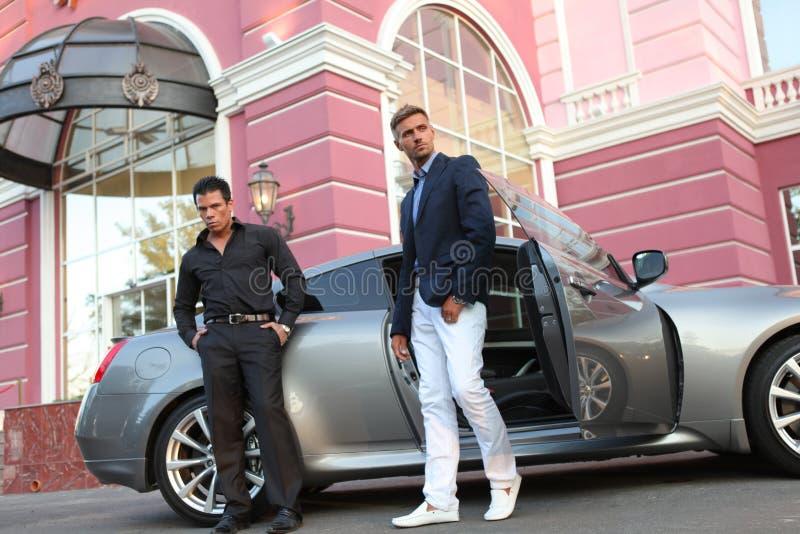 Due uomini d'affari si avvicinano all'automobile di lusso immagini stock libere da diritti