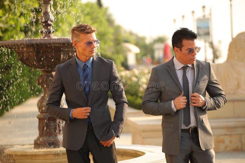 Due uomini d'affari si avvicinano alla fontana, occhiali da sole immagine stock