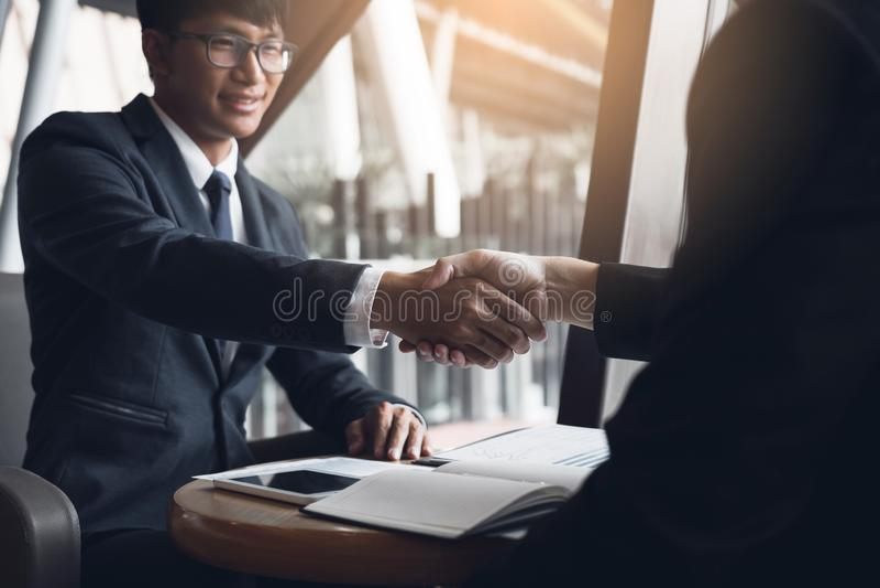 Due uomini d'affari sono parlanti e facenti gli affari sulle operazioni commerciali e acconsentire stringendo le mani nell'uffici immagine stock libera da diritti