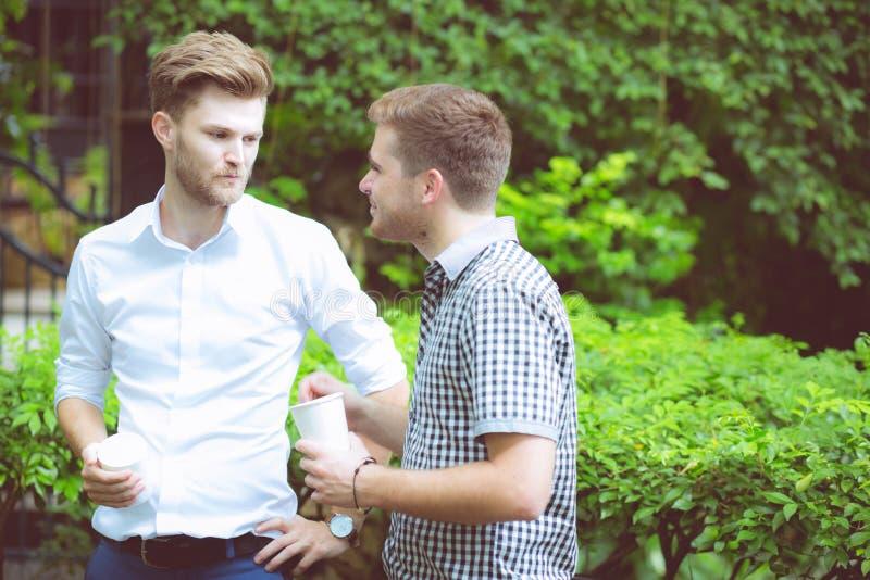 Due uomini degli amici che parlano stare in un giardino fotografie stock libere da diritti